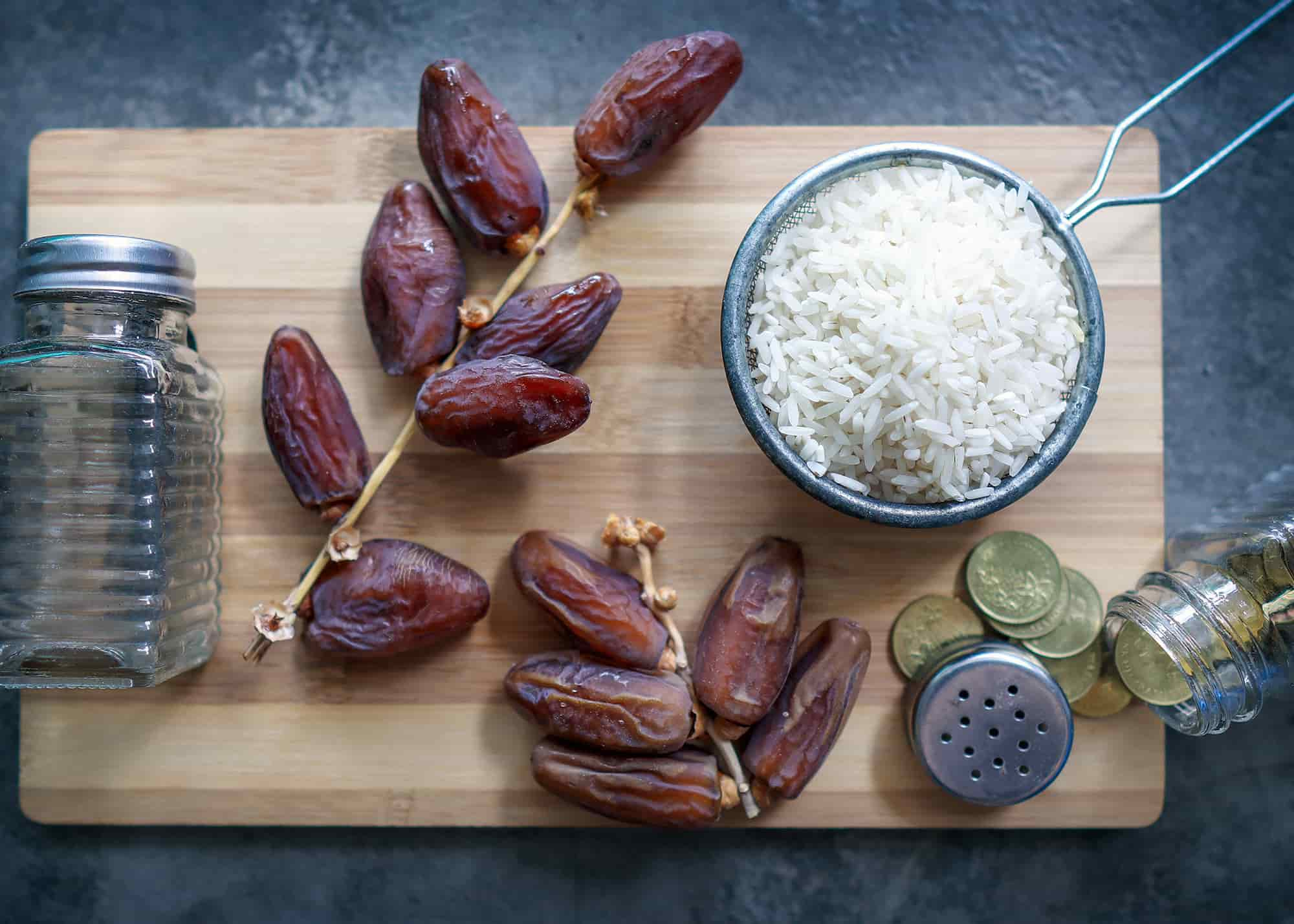 صورة تظهر مفهوم الزكاة في رمضان وتحوي الأرز والتمر وبعض العملات النقدية على رف خشبي